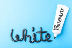 Pâte dentifrice noire de charbon de bois pour les dents blanches Exprimez le BLANC de la pâte dentifrice noire, tube sur le bleu  photo libre de droits