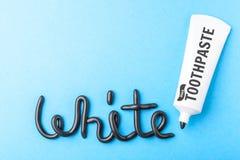 Pâte dentifrice noire de charbon de bois pour les dents blanches Exprimez le BLANC de la pâte dentifrice noire, tube sur le bleu  photographie stock