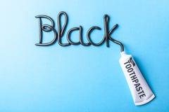 Pâte dentifrice noire de charbon de bois pour les dents blanches Exprimez le NOIR de la pâte dentifrice, tube sur le fond bleu photos libres de droits