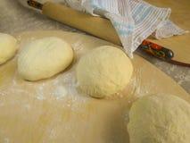 Pâte et farine sur un conseil en bois, une goupille et une serviette Photographie stock libre de droits