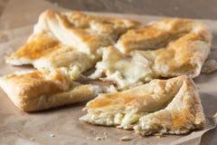 Pâte feuilletée avec du fromage sur un papier de cuisson Photo stock