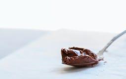 Pâte fondue de chocolat dans une cuillère sur un fond de pierre de whte Cl image stock