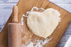 Pâte pour les gâteaux faits maison, en forme de coeur, sur un conseil en bois et une goupille une serviette avec un modèle sur un photo libre de droits