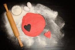 Pâte rouge avec un coeur découpé Oeufs et farine sur une table noire, goupille Photographie stock libre de droits