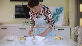 Pâte supérieure heureuse de biscuit de roulement de femme à la maison dans la cuisine clips vidéos