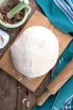 Pâte sur un conseil en bois et un fond de bois, de serviette verte et de farine image libre de droits