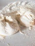 Pâte sur une table blanche avec de la farine image stock