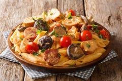 Pâtes épicées chaudes de penne avec le poulet frit, les champignons sauvages, la saucisse fumée, les tomates et le plan rapproché photos stock