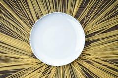 Pâtes autour du plat blanc sur la table en bois Photos libres de droits