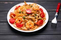 Pâtes avec des crevettes et des tomates Images stock