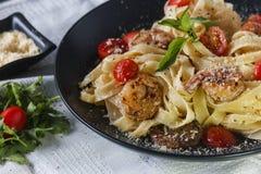 Pâtes avec des crevettes et des tomates-cerises sur le tissu Images stock