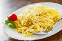 Pâtes avec du fromage râpé dans le plat blanc sur la table en bois photos libres de droits