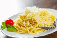 Pâtes avec du fromage râpé dans le plat blanc sur la table en bois images libres de droits