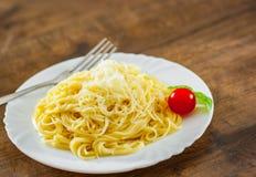 Pâtes avec du fromage râpé dans le plat blanc sur la table en bois image stock