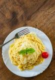 Pâtes avec du fromage râpé dans le plat blanc sur la table en bois photographie stock libre de droits