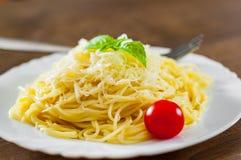 Pâtes avec du fromage râpé dans le plat blanc sur la table en bois photos stock