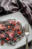 Pâtes avec l'encre noire de seiches et les petits poulpes Photos stock
