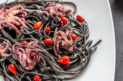 Pâtes avec l'encre noire de seiches et les petits poulpes Images stock