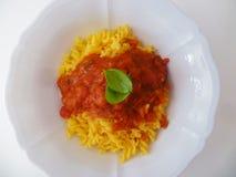 Pâtes avec la sauce tomate et basilic dans une cuvette en céramique blanche d'en haut Photos stock