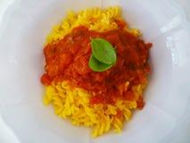Pâtes avec la sauce tomate et basilic dans une cuvette en céramique blanche d'en haut Image stock