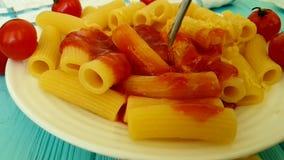 Pâtes avec le ketchup, tomates-cerises, fourchette traditionnelle de consommation, tir au ralenti banque de vidéos