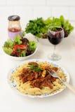 Pâtes avec le sause de viande, la salade verte et le vin Image stock