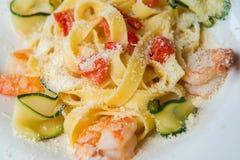 Pâtes avec les crevettes, la courgette, les tomates et le parmesan Image stock