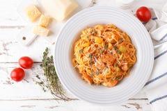 Pâtes bolonaises de spaghetti avec la sauce tomate, les légumes et la viande de poulet sur le fond rustique en bois blanc Les FO  image stock