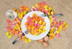 Pâtes colorées de ravioli avec un plat blanc, deux fourchettes, trois oeufs et un verre de l'eau sur la toile Photographie stock libre de droits
