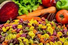 Pâtes colorées sur une table avec des betteraves de légumes frais, verts, carottes, tomates, poivrons Photographie stock libre de droits