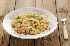 Pâtes crémeuses avec les saumons et le persil dans le plat blanc Photographie stock