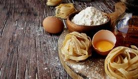 Pâtes crues avec de la farine sur la table, foyer sélectif photos stock