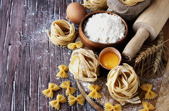 Pâtes crues avec de la farine sur la table, foyer sélectif Photographie stock libre de droits
