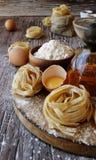 Pâtes crues avec de la farine sur la table, foyer sélectif Image stock