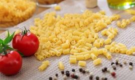 Pâtes crues de macaronis avec des tomates Photos libres de droits