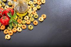 Pâtes crues de tortellini sur le fond noir Image stock