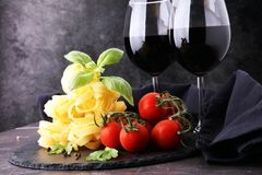 Pâtes crues et tomates-cerises rouges fraîches avec le basilic Photos libres de droits