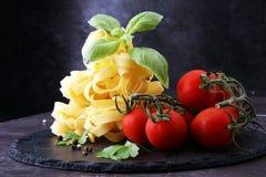 Pâtes crues et tomates-cerises rouges fraîches avec le basilic Photographie stock libre de droits
