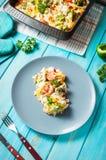 Pâtes cuites au four avec le brocoli et la sauce tomate de fromage sur le fond en bois bleu Photos stock