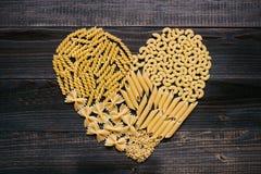 Pâtes d'amour Pâtes sèches dans la forme de coeur sur la table en bois foncée, vue supérieure Images libres de droits