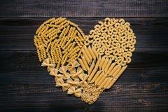 Pâtes d'amour Pâtes sèches dans la forme de coeur sur la table en bois foncée, vue supérieure Image stock