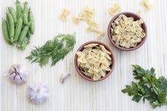 Pâtes dans un pot d'argile, des pois, des herbes et des épices Images stock
