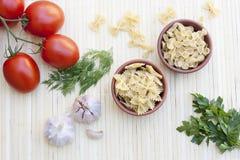 Pâtes dans un pot d'argile, des pois, des herbes et des épices Photo stock