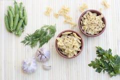 Pâtes dans un pot d'argile, des pois, des herbes et des épices Photos libres de droits