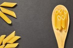 Pâtes dans une cuillère en bois sur un fond blanc Photo stock
