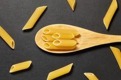 Pâtes dans une cuillère en bois sur un fond blanc Images stock