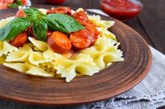 Pâtes de Farfalle dans une cuvette en céramique, service avec le ketchup, tomates fraîches, saucisse en sauce tomate Image libre de droits