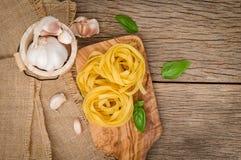 Pâtes de Fettuccine installées sur le bois de coupe Pâtes de Fettuccine ingred photographie stock