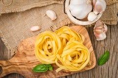 Pâtes de Fettuccine installées sur le bois de coupe Pâtes de Fettuccine ingred photo libre de droits