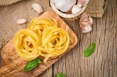 Pâtes de Fettuccine installées sur le bois de coupe Pâtes de Fettuccine ingred photographie stock libre de droits